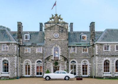 Photo of the front of Farleigh House with a Bentley outside